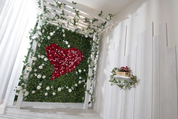 ウェディング写真の撮影に人気な、沢山のお花で装飾された素敵なフォトスタジオ♪中央に描かれているハートマークがポイントです♪